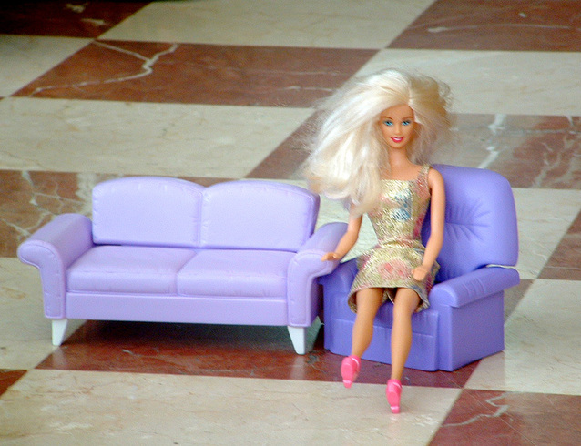 panenka Barbie sedící na modré pohovce